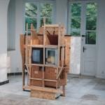 R.Rychter, EPITAFIUM DLA MARII obiekt, 2005 r. wymiary: 250x180x50 cm materiał: szumiący telewizor, zdjęcie Jana Pawła II, listwy drewniane, meble iprzedmioty pomojejbabci.